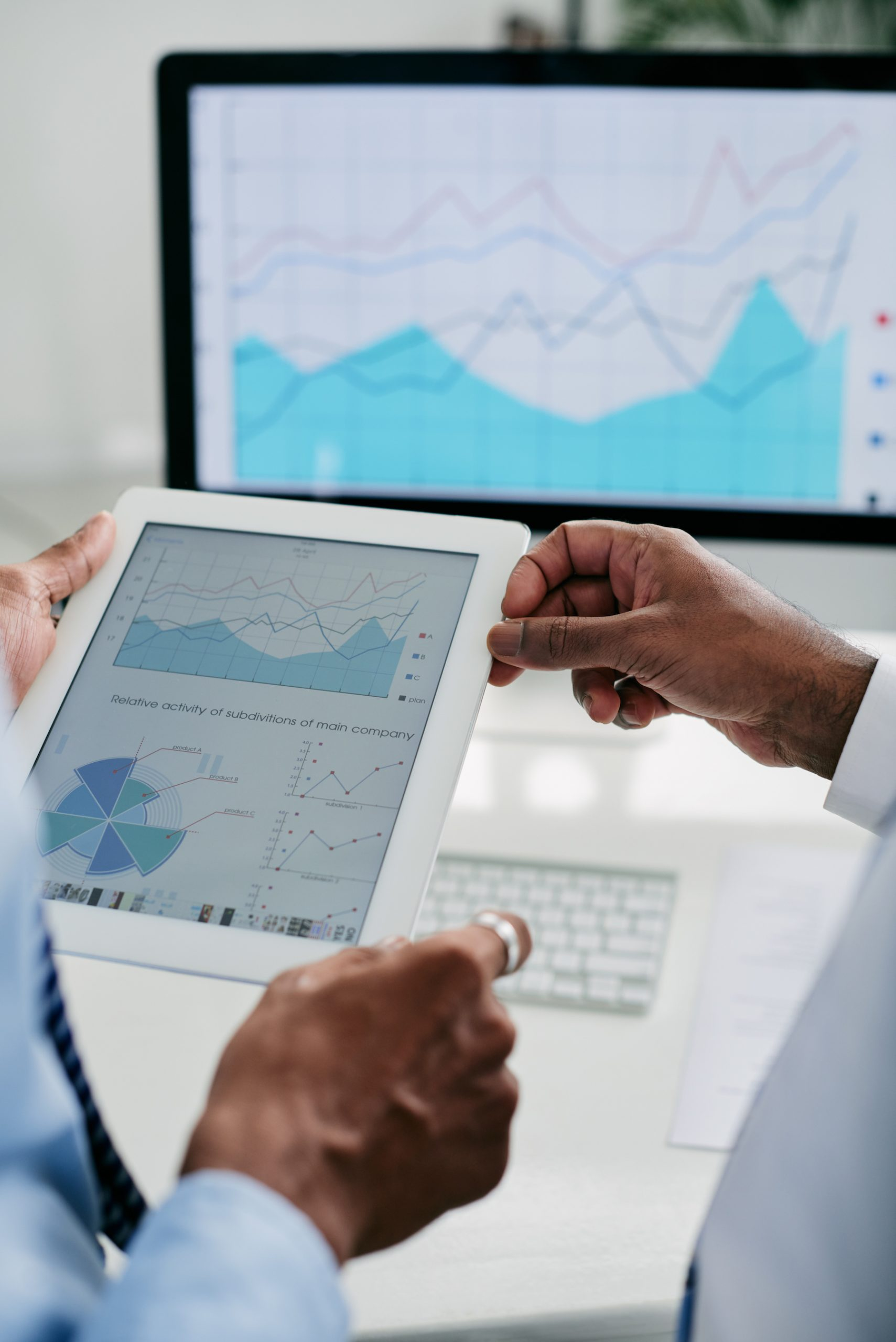 Document with financial diagram on tablet computer in hands of business executives